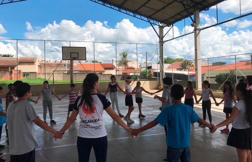 Em quadra escolar coberta, estudantes e educadora formam um círculo com mãos dadas. Ao centro da roda, estudante participa de jogo vendada. Fim da descrição