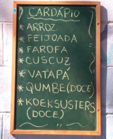 Lousa com cardápio de comidas: arroz, feijoada, cuscuz, vaatapá, qumbe (doce), koeksusters (doce). Fim da descrição.