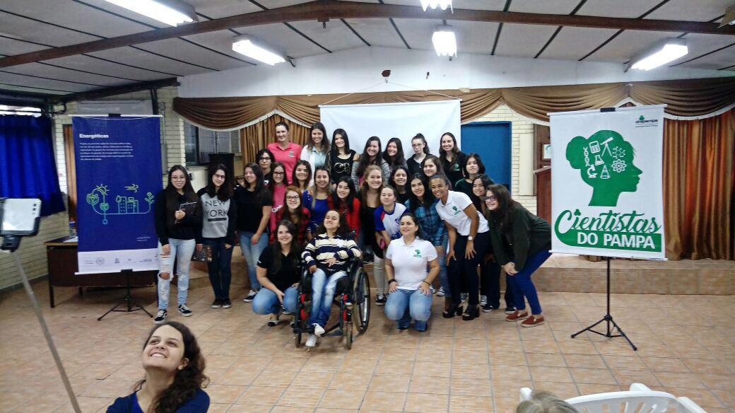 """Em auditório, várias mulheres e jovens posam para a foto. Do lado direito, cartaz com logo do """"Cientistas do Pampa"""". Fim da descrição."""