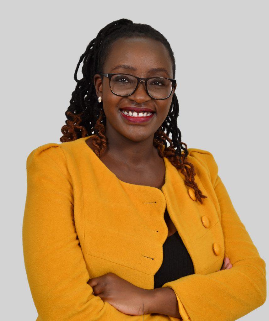 Foto da cintura para cima de Maria Omare. Ela é uma mulher negra, com cerca de 30 anos. Seu cabelo tem tranças enraizadas e veste um terno amarelo com botões. Fim da descrição.