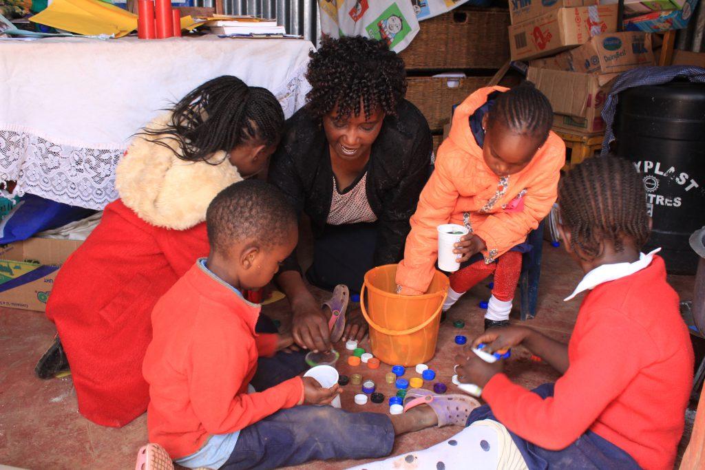 Acompanhadas por educadora e sentadas em chão, quatro crianças brincam com tampinhas coloridas de garrafa retiradas de balde laranja. Ao fundo, caixas de papelão amontoadas no canto direito contrastam com livro sobre a mesa no canto esquerdo. Fim da descrição.