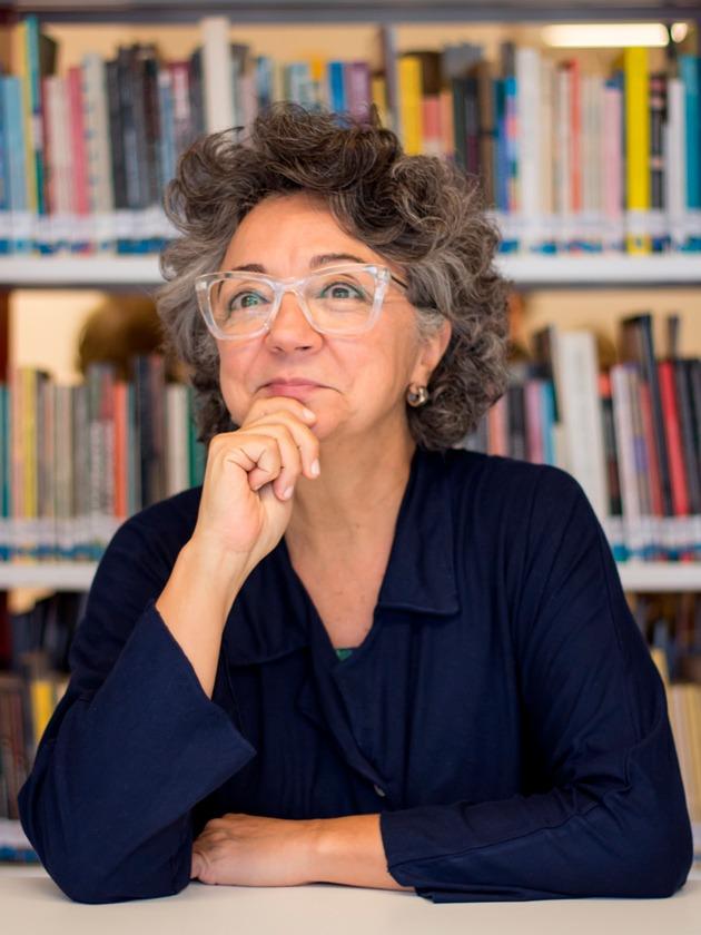 Em frente a estante de livros, Tereza Perez posa para foto. Ela usa óculos e blusa azul e coloca a mãe direita no queixo para a pose, enquanto a poia a esquerda  sobre mesa. Ela está na faixa dos 50 anos e tem cabelos grisalhos. Fim da descrição.