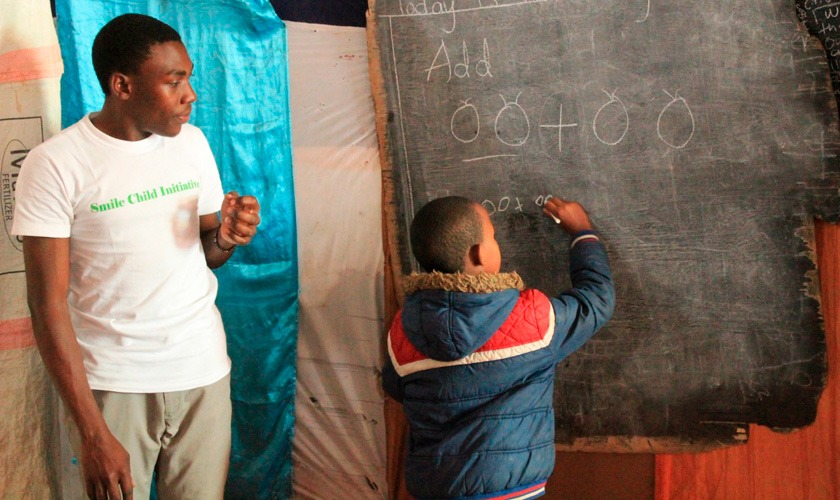 """Em lousa de madeira improvisada, criança escreve com giz branco, realizando exercícios de álgebra com desenhos. Ao lado, educador o observa vestindo uma camisa branca com os dizeres """"smile child initiative"""". Fim da descrição."""