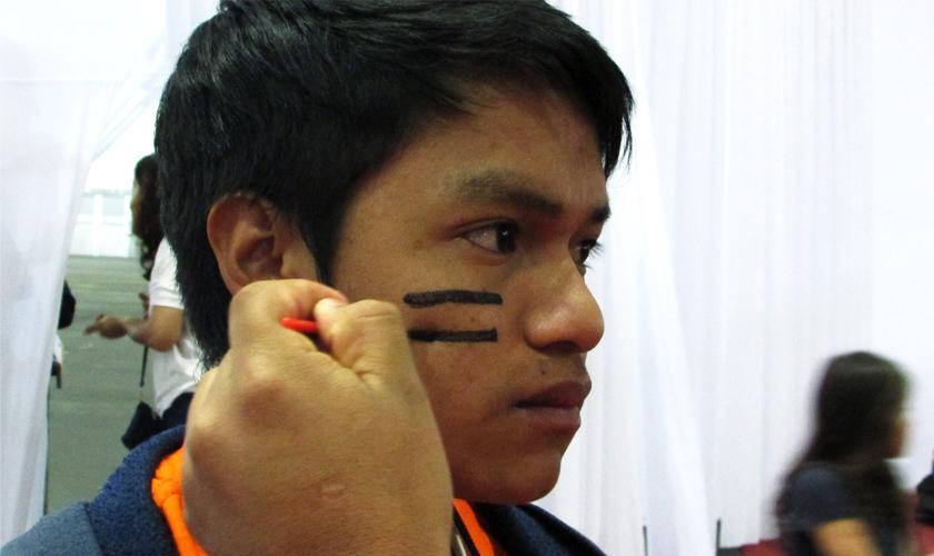 Jovem indígena tem o rosto pintado com duas faixas pretas na bochecha. Fim da descrição.