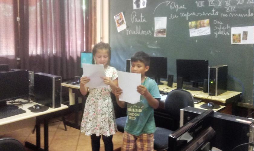 Em sala com computadores, duas crianças fazem leitura de papéis em suas mãos. Ao fundo, lousa verde com colagens e escritos de giz. Fim da descrição.