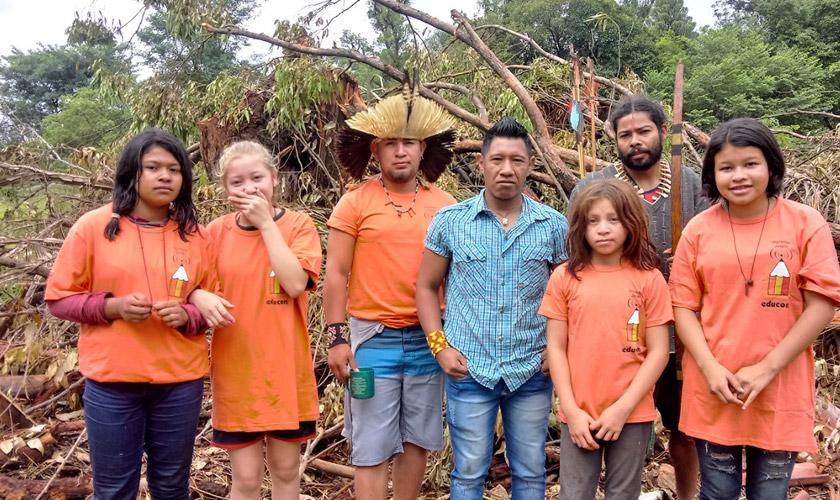 """Três adultos e quatro crianças indígenas participam de atividade ao ar livre. Cinco deles usam camisetas da cor laranja, escrito """"educom"""". Ao centro, indígena utiliza adorno de cabeça tradicional; à direita, homem segura arco de madeira. Fim da descrição."""