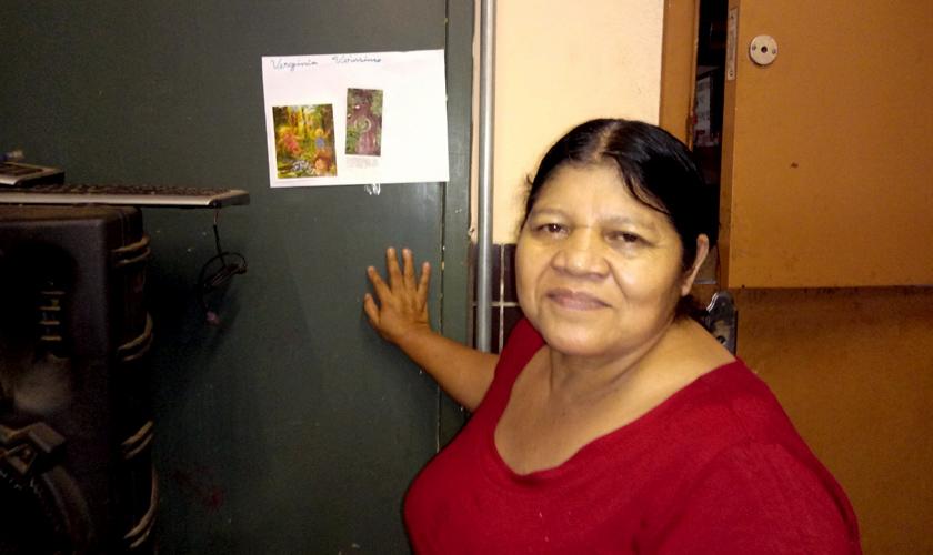 Mulher indígena sorri para a câmera; sua mão está apoiada sobre lousa verde, onde está colado um papel com duas fotos menores. Fim da descrição.