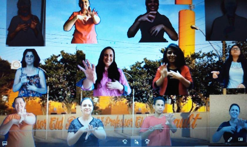 Imagem retirada do vídeo. Em fundo de fachada da Escola Estadual Cid Boucault, a imagem de 12 pessoas da escola aparecem recortadas, cada uma delas faz um gesto em Libras. Fim da descrição.