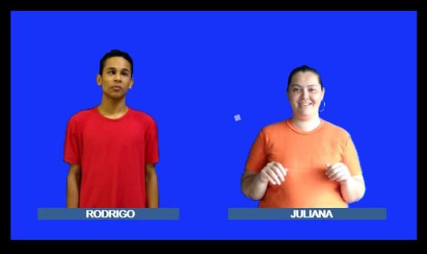 Imagem retirada do vídeo. Em fundo azul, lado a lado estão o aluno Rodrigo e a professora Juliana, intérprete de Libras. Rodrigo é um homem negro na faixa dos 15 anos e veste camisa vermelha, enquanto Juliana é uma mulher branca na faixa dos 30 anos e Ela veste uma camisa laranja. Fim da descrição.