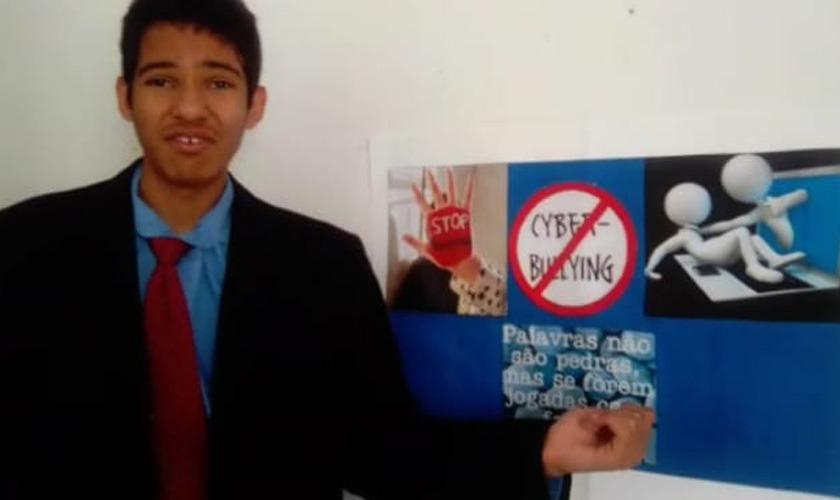Estudante vestido de terno e gravata aponta para painel contra ciberbulliying. Fim da descrição.