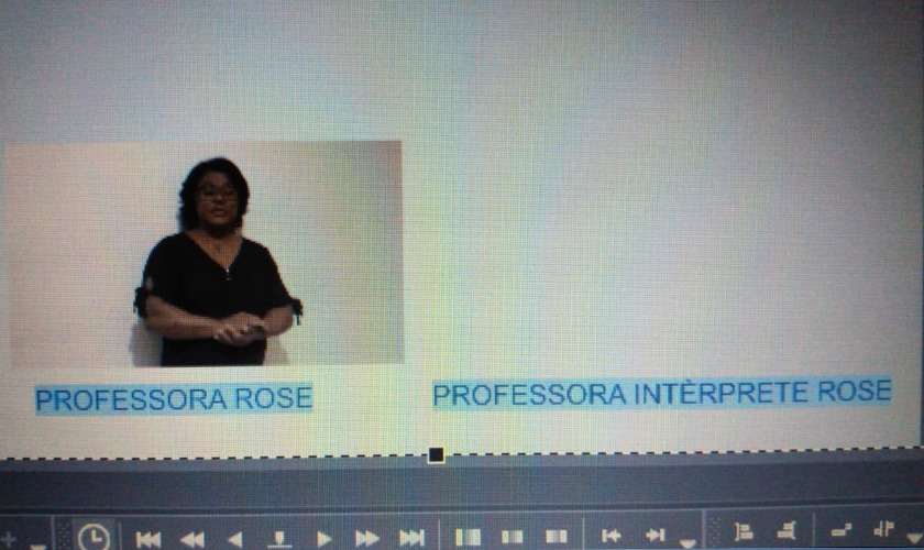 """Imagem de programa de edição do vídeo. Há duas caixas retangulares lado a lado. Na da esquerda, mulher negra vestida de camisa preta faz gestos com as mãos. Abaixo se lê """"Professora Rose"""". Ao lado, uma caixa de texto com a informação """"Professora Intérprete Rose"""". Fim da descrição."""
