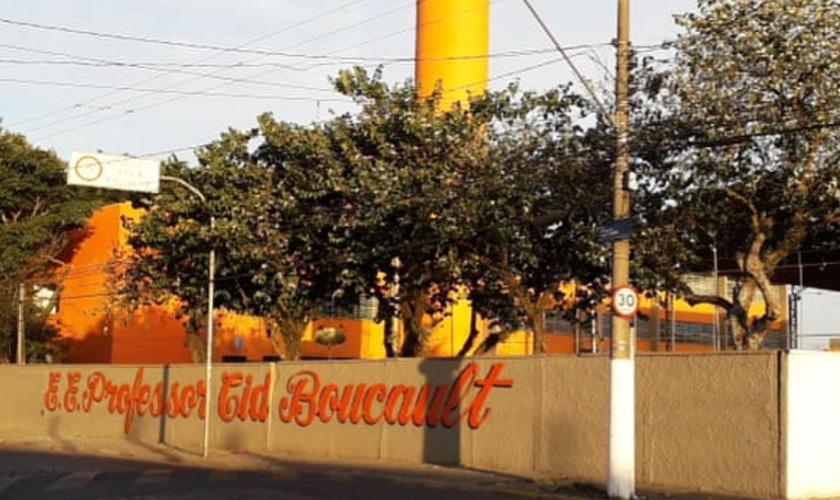 Fachada da Escola Estadual Cid Boucault. O nome da escola está escrito na cor laranja em muro escolar. Atrás, uma árvore e uma pilastra amarela. Fim da descrição.