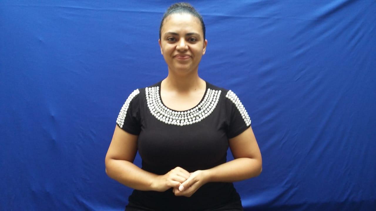 Imagem da professora Kelly em fundo azul para a gravação do vídeo. Ela faz gestos de Librasé uma mulher negra na faixa dos 30 anos, usa um coqui no cabelo e veste uma camisa preta. Fim da descrição.