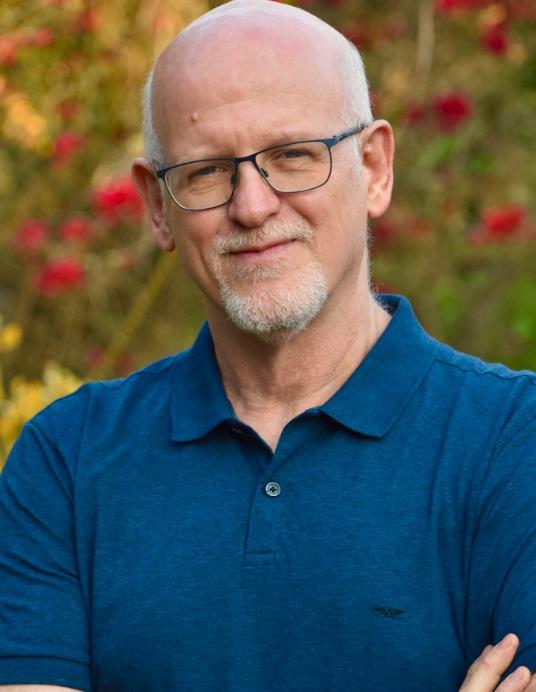 Em frente a árvore, Daniel Becker veste camisa polo azul e cruza os braços para as fotos. É um homem na faixa dos 50 anos, com cabelos brancos. Usa cavanhaque e óculos.