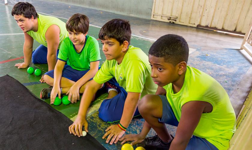 Em quadra esportiva, quatro estudantes uniformizados estão sentados no chão e participam de jogo. Três deles têm duas bolas coloridas à sua frente; o outro aluno segura uma bola menor, da cor branca. Fim da descrição.