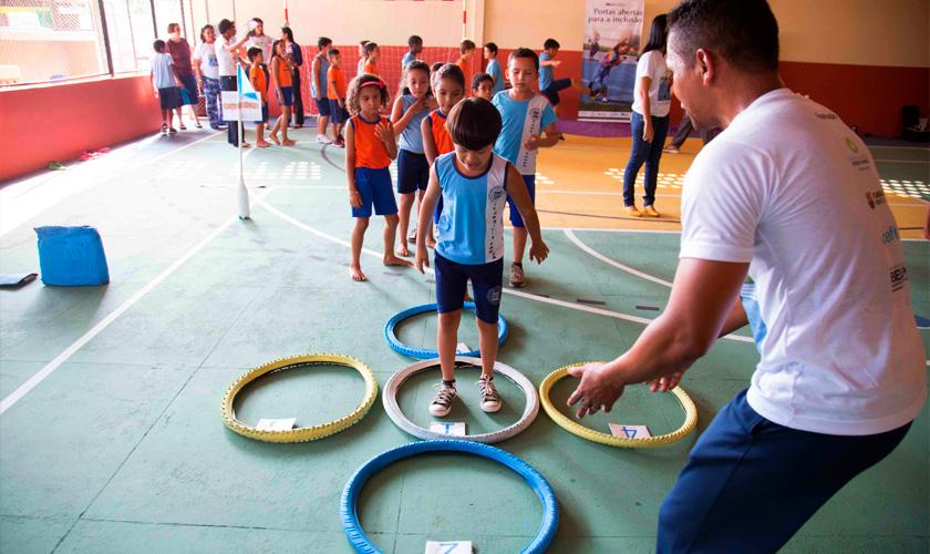 Em quadra esportiva, dezenas de crianças participam de circuito com diferentes atividades físicas. À frente, educador acompanha estudante, que está dentro de um círculo branco no chão. Ao redor dele, há outros quatro círculos nas cores amarelo e azul. Fim da descrição.