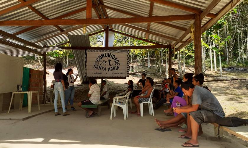 """Indígenas em estrutura de madeira em local aberto estão sentados em cadeiras e bancos enquanto observam duas mulheres que estão de pé falarem. Ao fundo, painel escrito em preto """"Comunidade Santa Maria"""". Fim da descrição."""