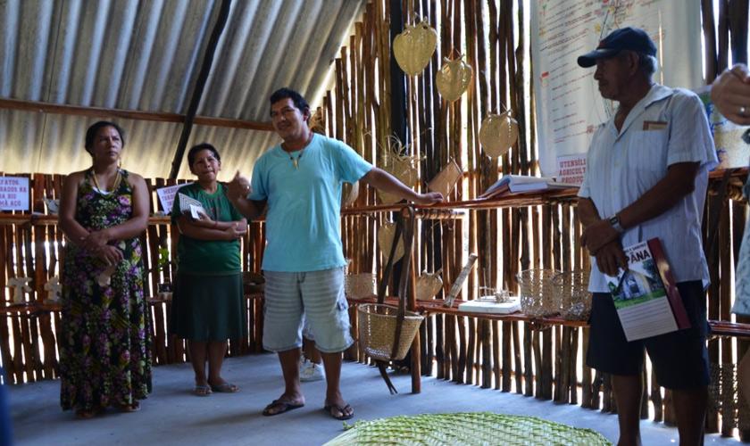 Dentro de estrutura com paredes de madeira, três pessoas observam homem falar ao centro. Ao fundo, diversos objetos artesanais. Fim da descrição.