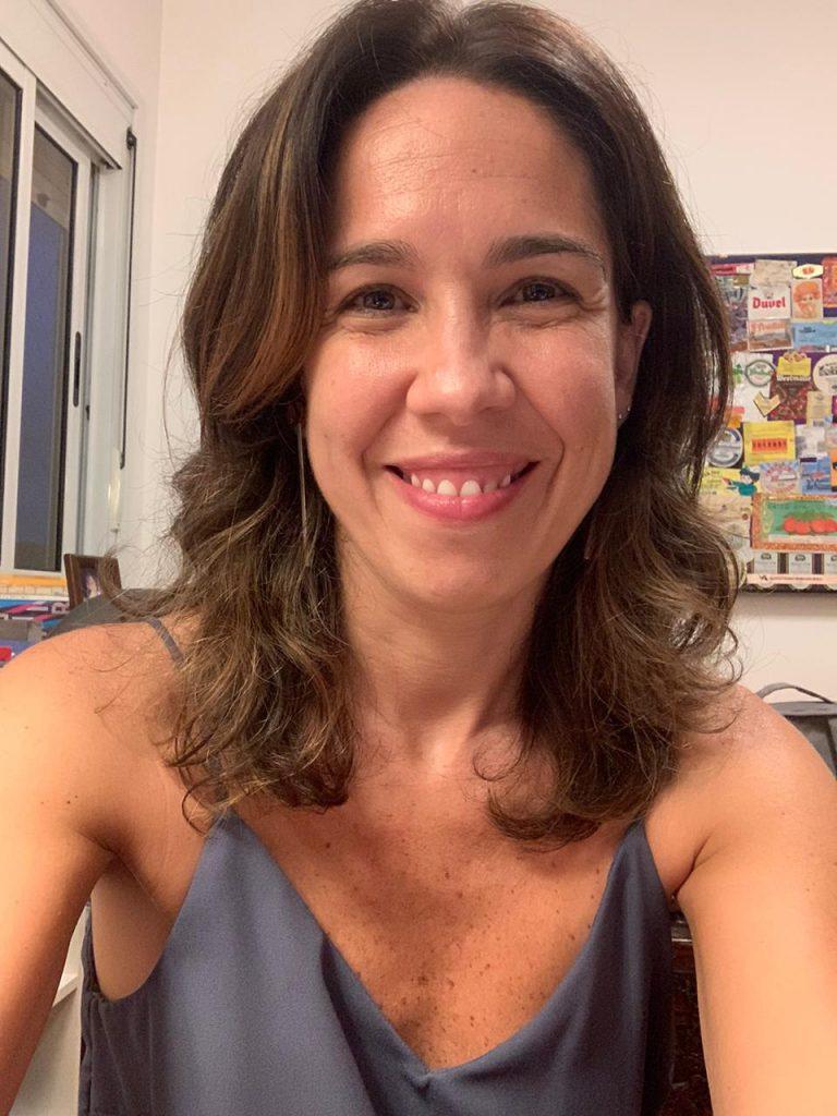 Em sala de escritório, Natacha Costa sorri para foto com uma camisa azul. Ela é uma mulher branca na faixa dos 30 anos de idade e está com os cabelos soltos. Fim da descrição.