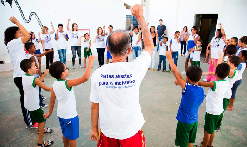 """Em quadra esportiva, crianças, jovens e adultos estão em pé em círculo e participam de atividade juntos. À frente da câmera, homem de costas veste camiseta branca escrito """"Portas abertas para a inclusão"""". Fim da descrição."""