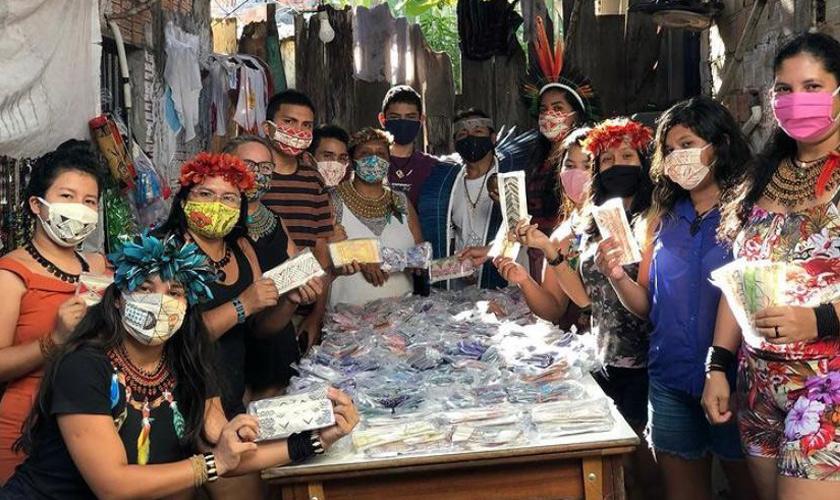 Em volta de mesa, catorze indígenas posam para a foto segurando máscaras plastificadas. Sobre a mesa, dezenas de máscaras feitas à mão. Fim da descrição.