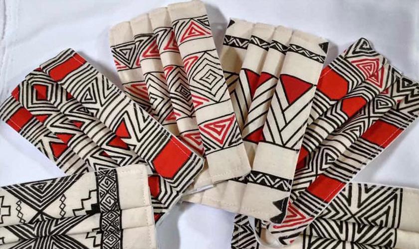 Máscaras de tecido com estampas indígenas nas cores preto e vermelho. Fim da descrição.