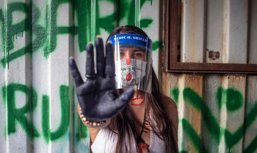 Indígena Samela Sateré Mawé com a mão pitada de preto aberta e erguida em direção à câmera. Ela utiliza máscara e protetor facial. Fim da descrição.