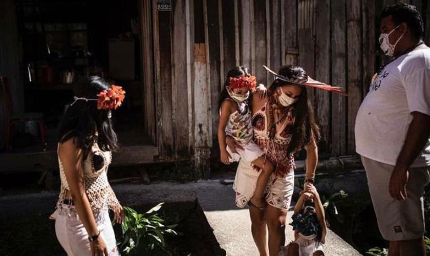Duas mulheres indígenas aparecem na foto. Uma delas leva uma criança no colo, enquanto outra criança abaixada pega em sua mão. As mulheres e as crianças vestem roupas e acessórios tradicionais. À direita da foto, homem observa a cena. Todos estão usando máscaras. Fim da descrição.