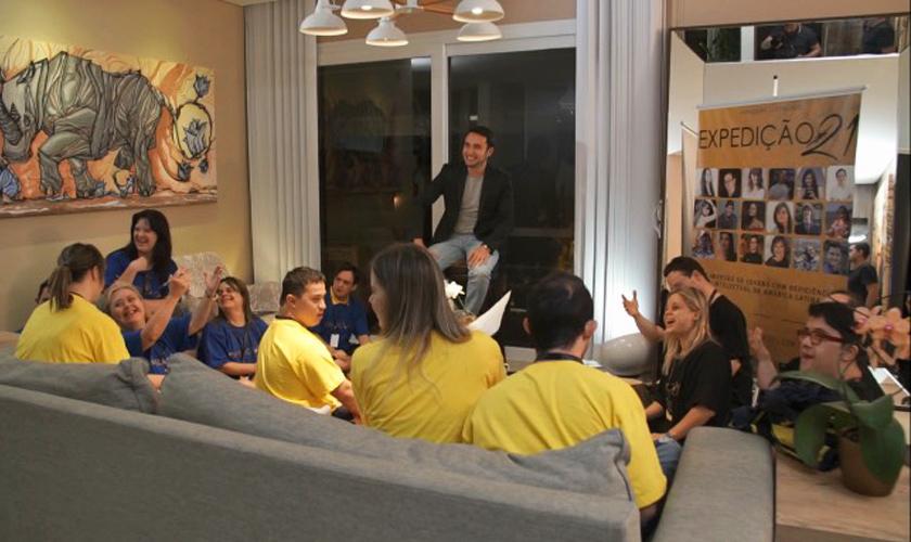 Em sala de estar, diversos jovens e adultos com síndrome de down estão sentados à volta de Alex Duarte. A maioria deles sorri. Alguns vestem camiseta azul, outros vestem blusa amarela e outros, preta. Fim da descrição.