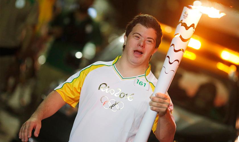 """Vestindo uniforme escrito """"Rio 2016"""" e logo das Olimpíadas em prata, Breno Viola carrega tocha acesa em uma das mãos. Fim da descrição."""