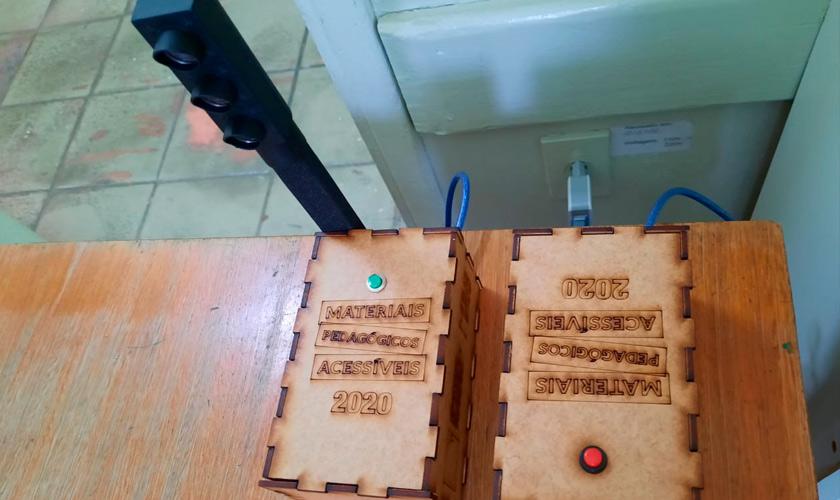 Sobre mesa, duas caixas de MDF utilizadas na realização do MPA. À esquerda, caixa eletrônica do semáforo. À direita, caixa sonora com um botão vermelho para reprodução. Fim da descrição.