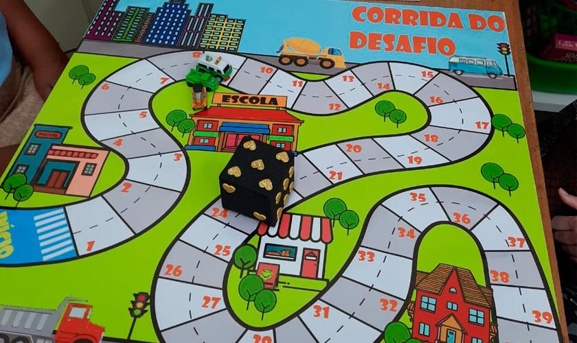 """Jogo de tabuleiro com ilustração de ruas, veículos, casas e comércios. Na parte superior do tabuleiro, texto """"corrida do desafio"""". Sobre o jogo, dado de EVA preto com numeração dourada. Fim da descrição."""