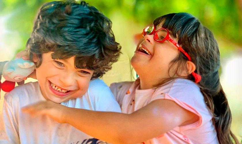 Alice, que está sorrindo e usa óculos vermelhos, abraça o irmão Antônio, que dá risada. Fim da descrição.