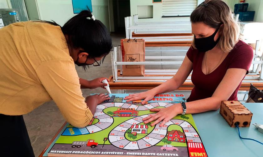 Duas educadoras usando máscara se apoiam na construção do tabuleiro do jogo. Uma delas passa cola no material, enquanto a outra estica banner com ilustração da trilha. Fim da descrição.