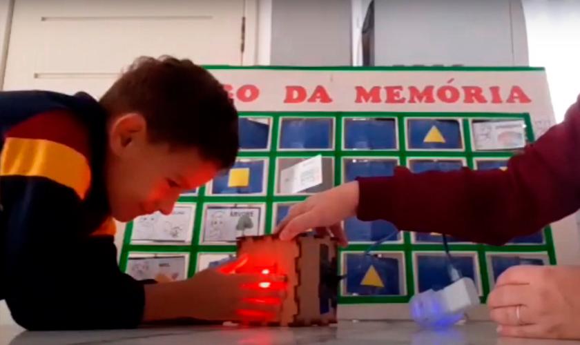 Em casa, estudante aperta botão de dado eletrônico enquanto sorri. Sua mãe o auxilia. Ao fundo, painel de Jogo da memória. Fim da descrição.