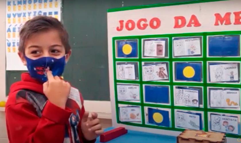 Em sala de aula, estudante utilizando máscara utiliza o material pedagógico acessível. O menino imita uma figura do painel, gesticulando para o nariz. Fim da descrição.