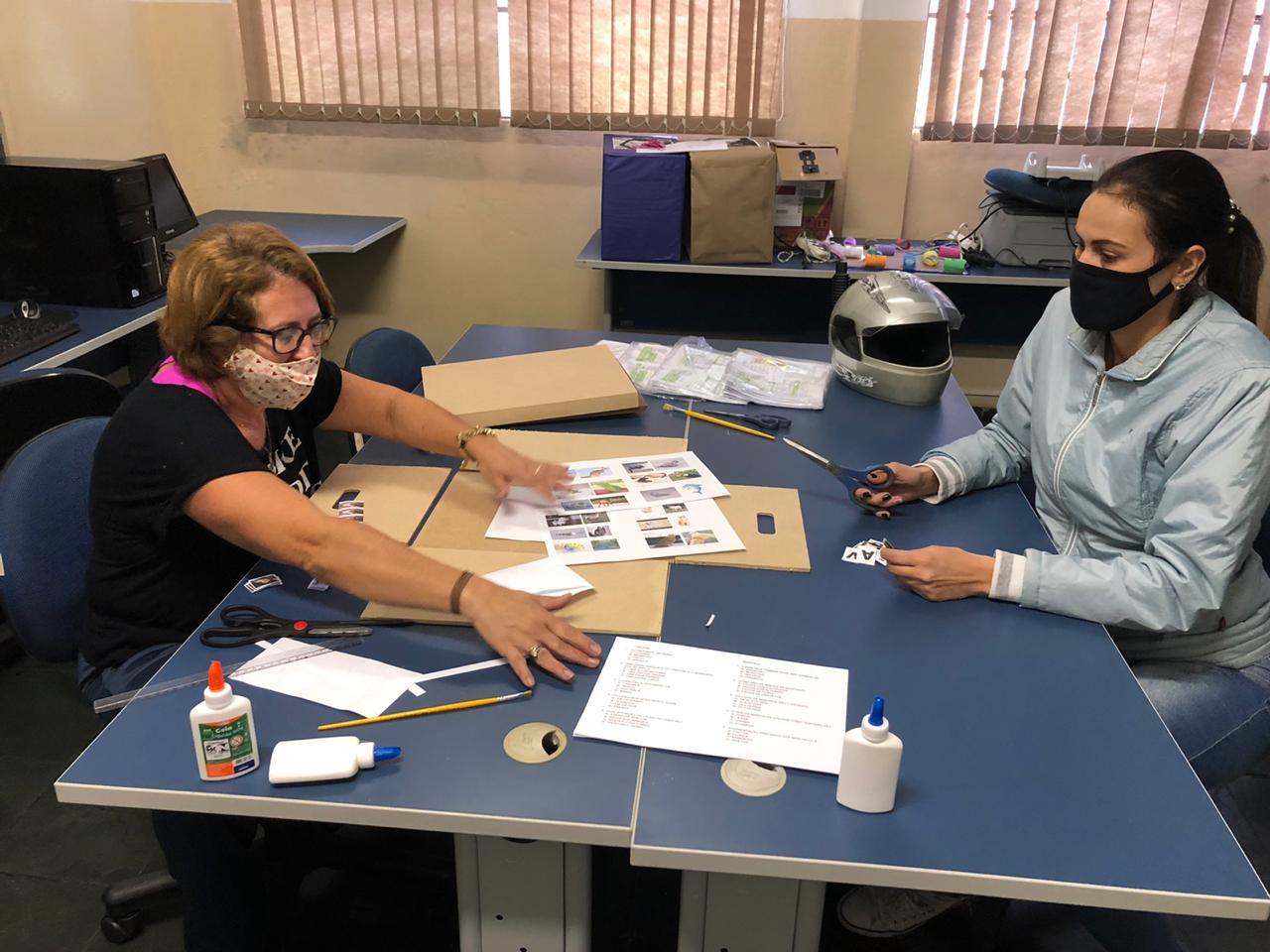 Sentadas ao redor de mesas retangulares azuis, duas educadoras com máscaras constroem o protótipo do material, utilizando pincéis, folhas de sulfite, colas e pedaços de material. Fim da descrição.