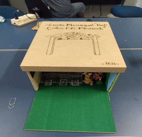 """Caixa do Meu passeio animal. Uma das paredes laterais, forrada com EVA verde, está aberta e revela animais de brinquedo no interior da caixa. Acima, na tampa, há um portal desenhado com o nome da escola: """"Escola Municipal Professora Girlene de Martinoli. Fim da descrição."""