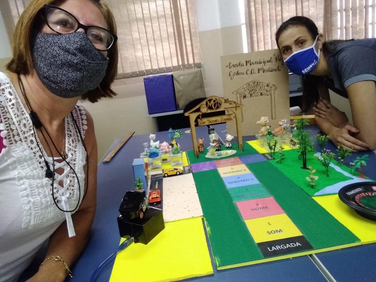 Em sala dos professores, duas educadoras utilizando máscaras tiram foto ao lado do jogo Meu passeio animal. Fim da descrição.