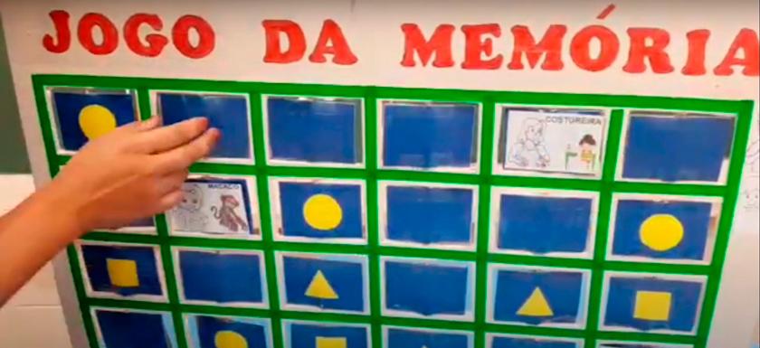 """Material pedagógico acessível escrito """"Jogo da memória"""" em rosa"""" na parte superior. O jogo é composto por um painel branco e placas na cor azul; algumas possuem desenhos de triângulos, círculos e quadrados. Fim da descrição."""
