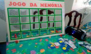 """Imagem da painel do Jogo da Memória. Há 24 retângulos vazados e contornados por adesivos verdes. Na parte superior, a inscrição """"Jogo da memória"""" pintado na cor vermelha. Fim da descrição."""