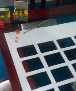 Estrutura de painel do Jogo da Memória sendo pintado com tinta branca. Fim da descrição.