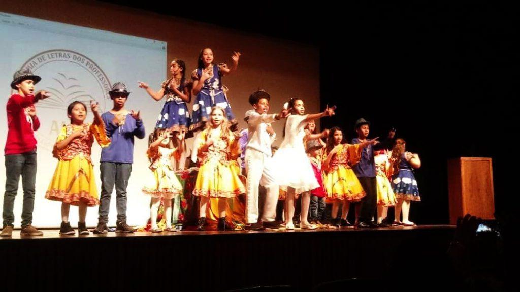 Em palco, estudantes com roupas típicas realizam apresentação artística em Seminário sobre Literatura de Cordel. Fim da descrição.