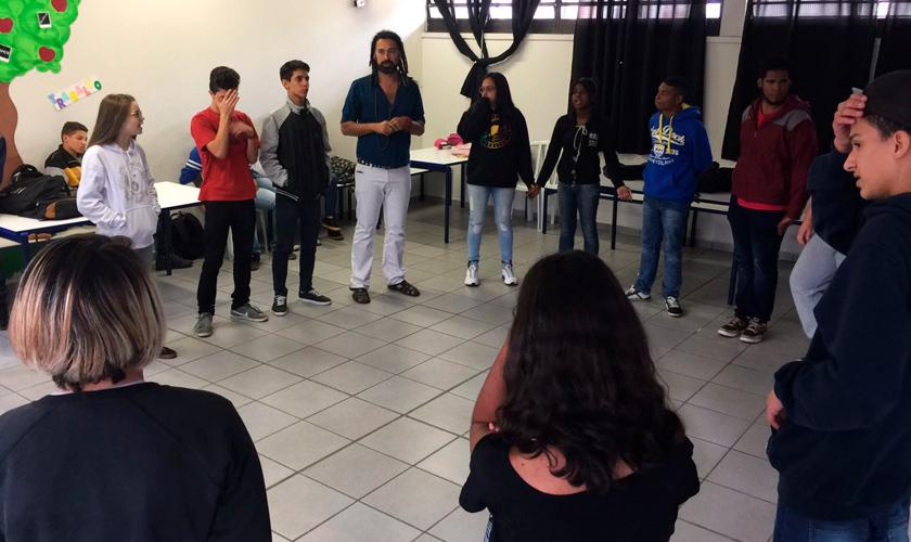 Estudantes conversam em sala de aula. Eles estão de pé, em um círculo. Fim da descrição.