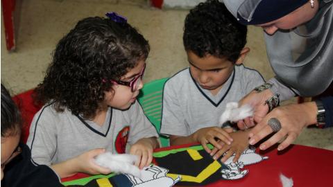 Menina e menino, sentados à mesa em sala de aula, fazem atividade com auxílio da professora. Fim da descrição.