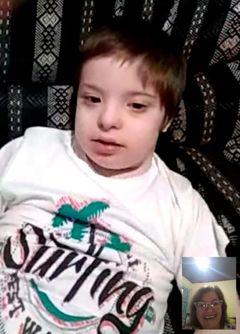 Criança com síndrome de down participa de video chamada com educadora, que aparece na tela em retângulo menor à direita. Fim da descrição.