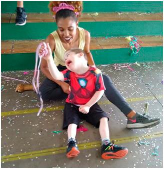 Sentados no chão de quadra esportiva, educadora e estudante dão risada. O menino segura fitas coloridas de papel. Fim da descrição.