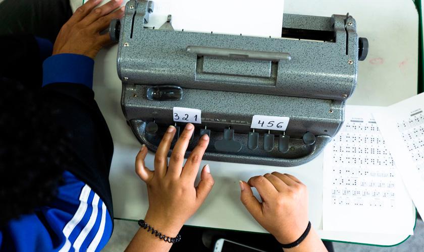 Em cima da mesa, mãos digitam em máquina braile. Fim da descrição.