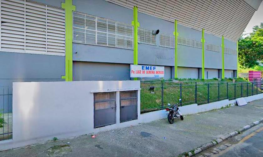 Fachada da escola municipal Padre Luiz de Oliveira Andrade, em Barueri. A escola possui muros muros externos brancos, enquanto os internos são azuis, e portões em azul escuro. Fim da descrição.