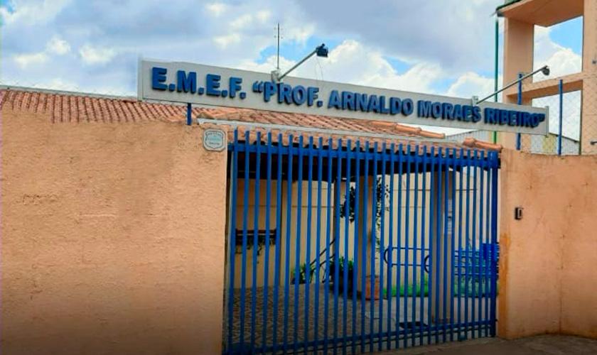 Fachada da escola Prof. Arnaldo Moraes Ribeiro, que tem muros amarelos e portão azul. Fim da descrição.